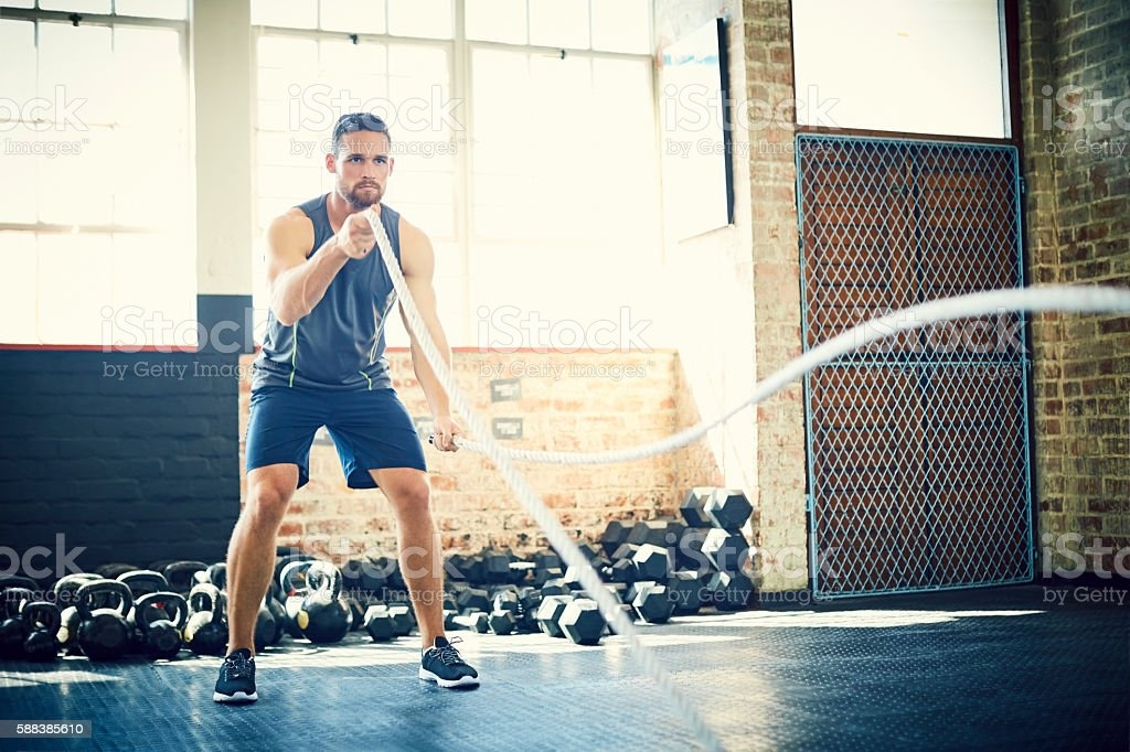 Determined man doing battling rope exercise in brightly lit gym stock photo