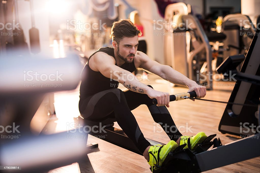 Determined man exercising on rowing machine in a gym. stock photo