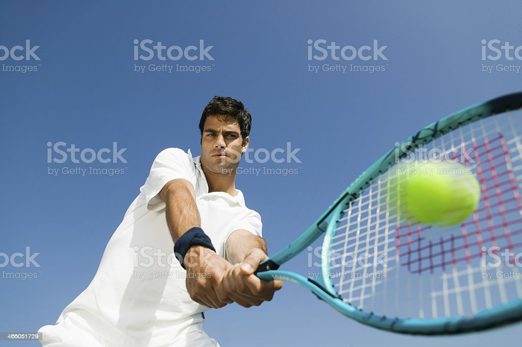 Determined Man Playing Tennis Against Sky stock photo