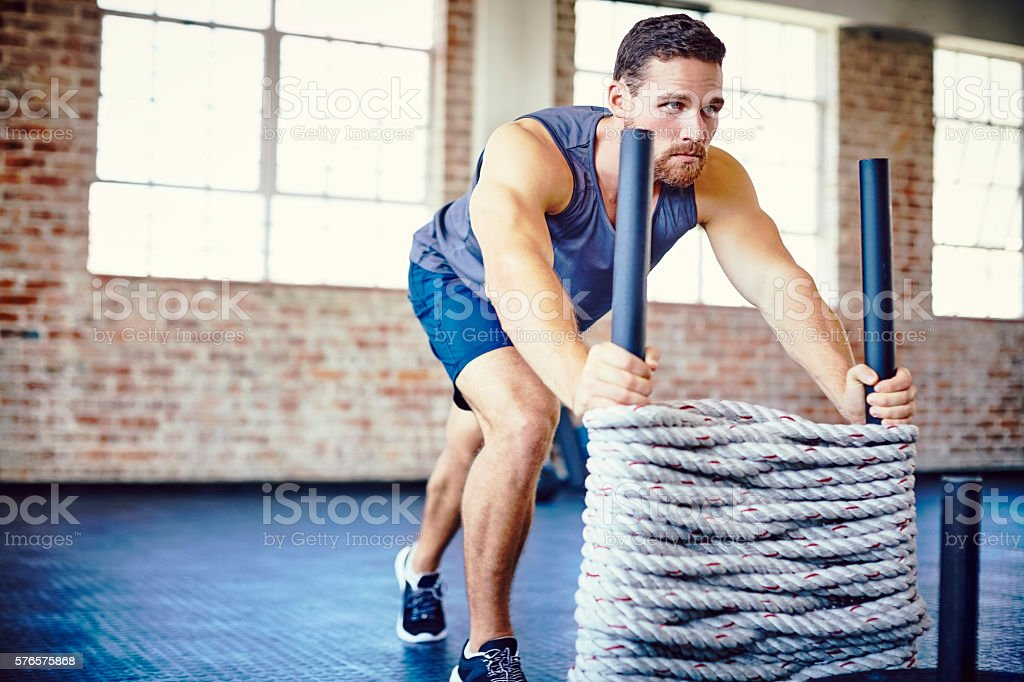 Determined sportsman exercising on rope sled in gym stock photo