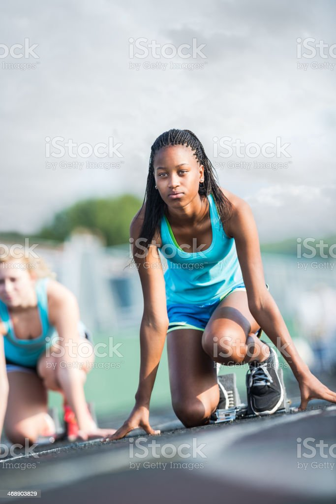 Determined Student Athlete at Starting Block of Race stock photo