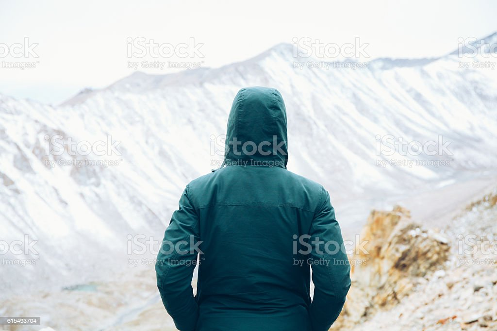 Determined traveler with hands in pocket in snow mountain stock photo