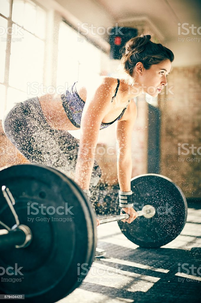 Determined woman deadlifting with barbell surrounded by chalk stock photo