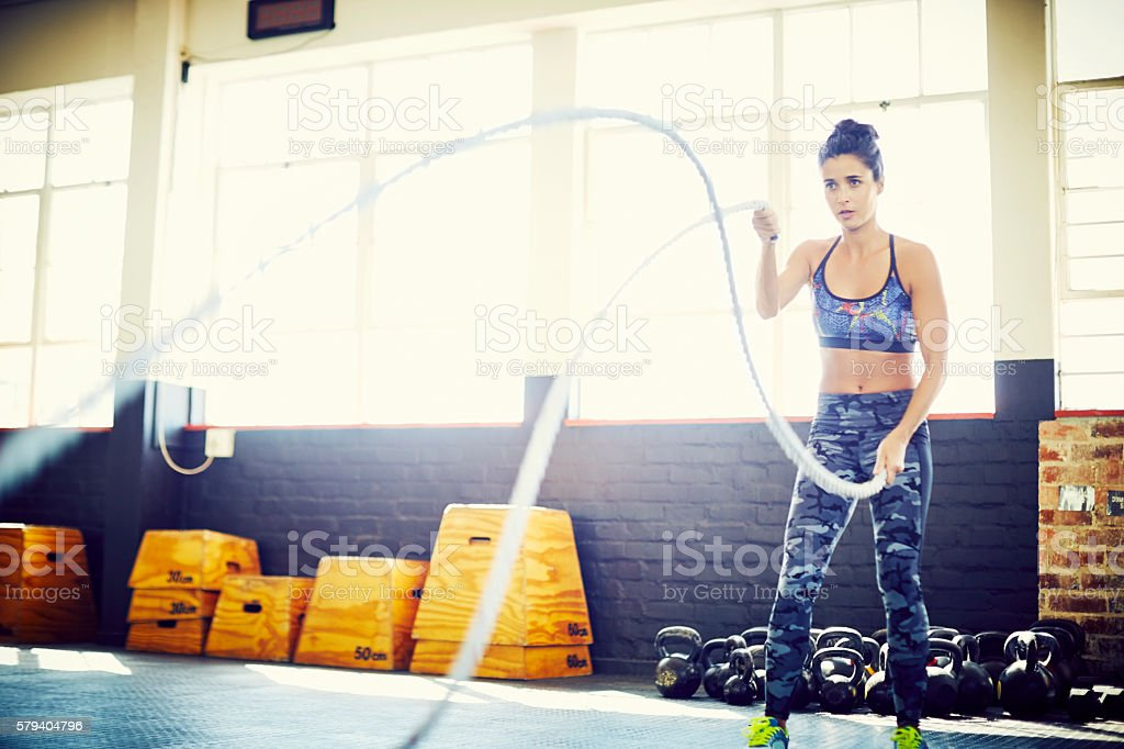 Determined woman doing battling ropes in training gym stock photo