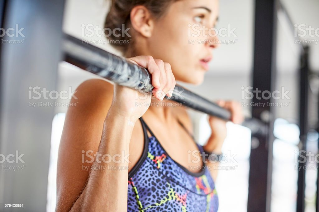 Determined woman doing chin ups on pull up bar stock photo