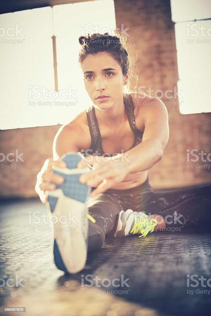 Determined woman doing stretching exercise in gym stock photo
