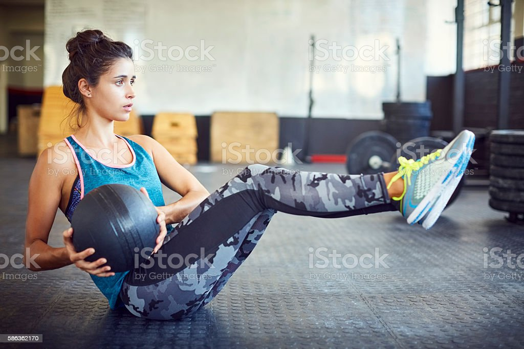Determined woman exercising with medicine ball in gym stock photo