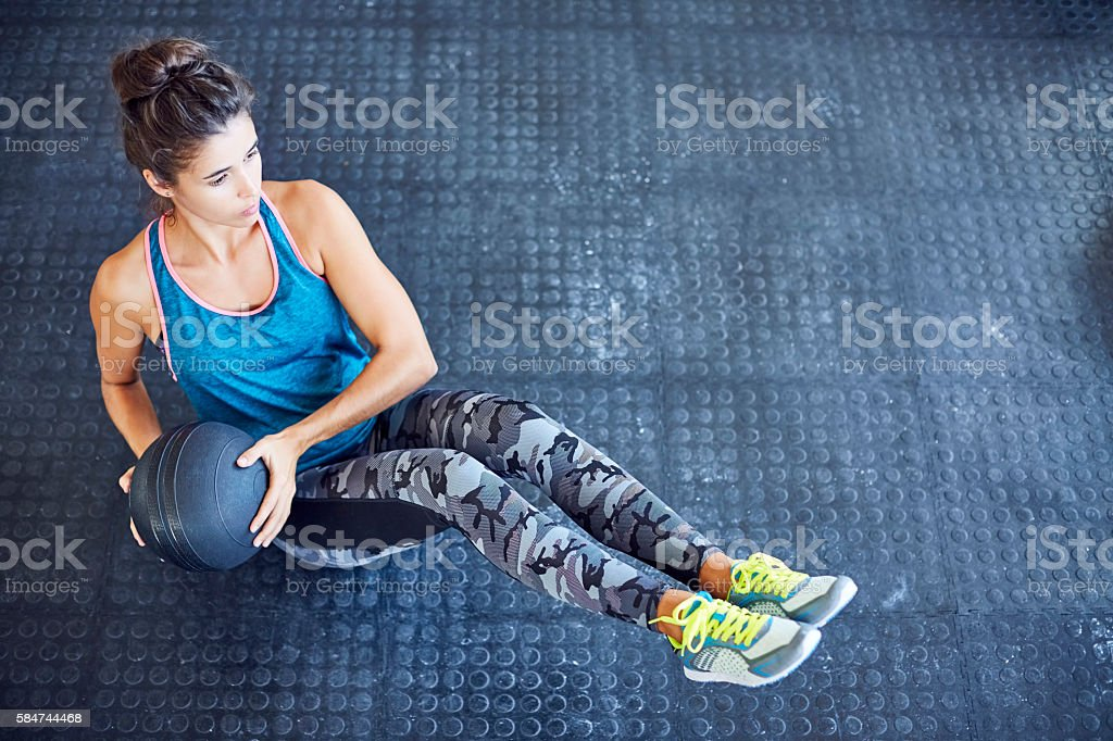 Determined woman exercising with medicine ball on gym floor stock photo