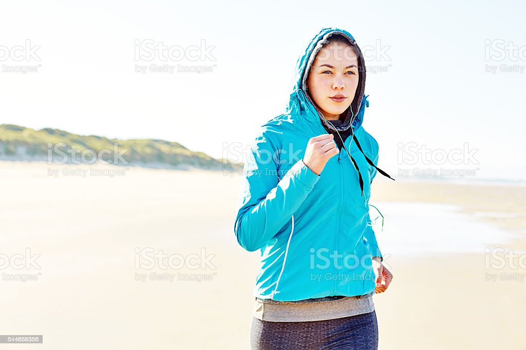 Determined woman in hooded jacket running on beach stock photo