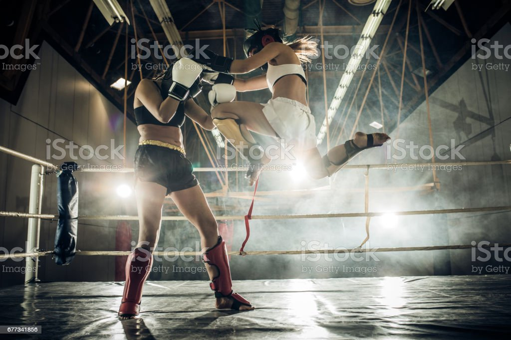 Determined woman making a flying move and kicking her opponent with a knee. stock photo
