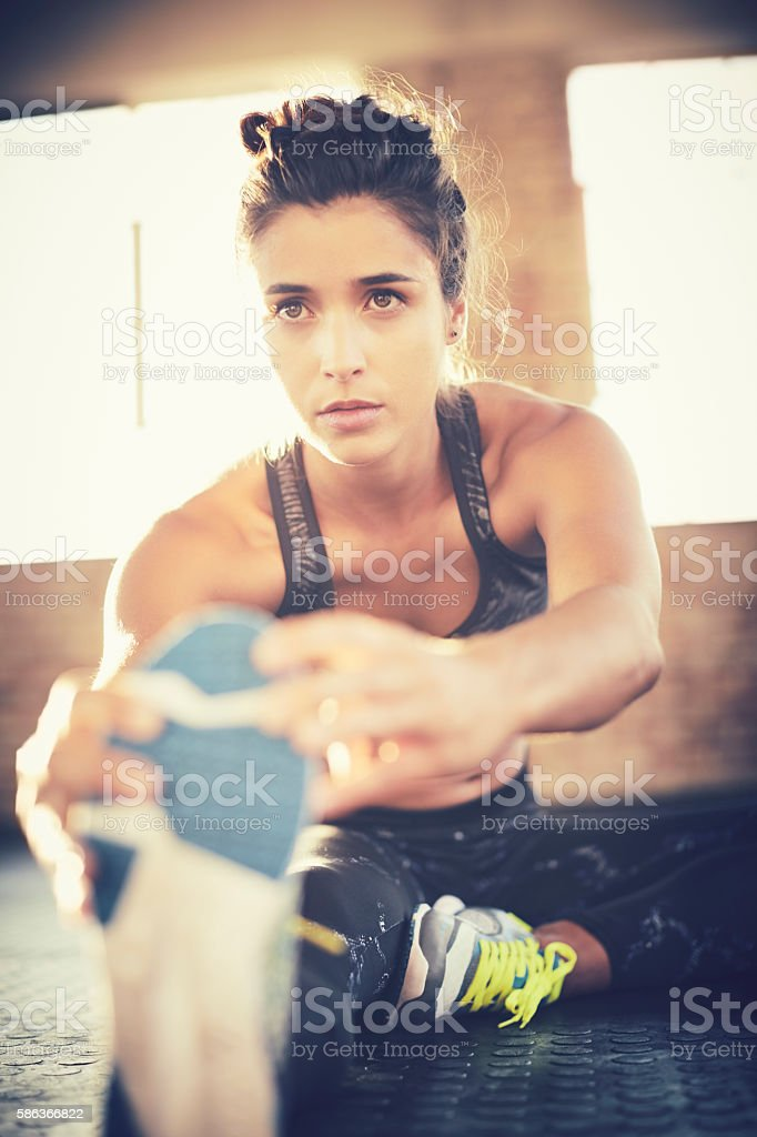 Determined woman performing stretching exercise in gym stock photo