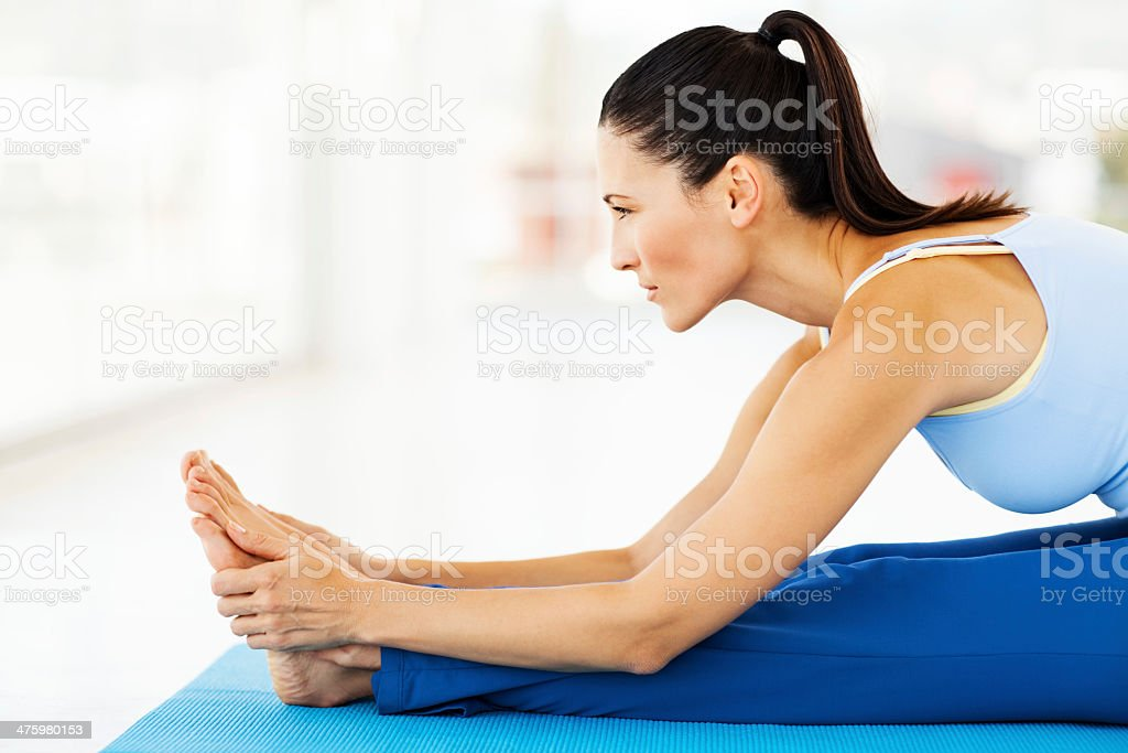 Determined Woman Practicing Yoga In Gym stock photo