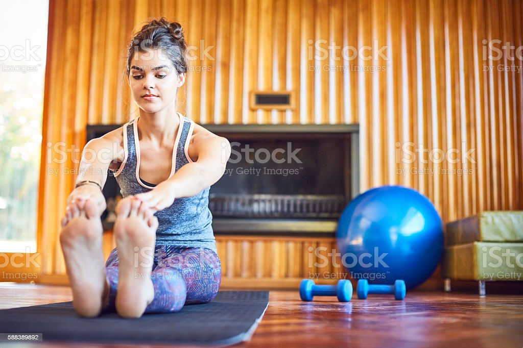 Determined woman stretching toe touch exercise at home stock photo