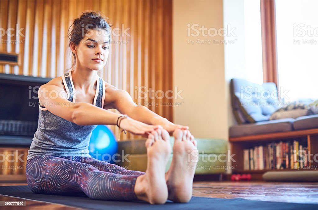 Determined woman stretching toe touch exercise on mat at home stock photo