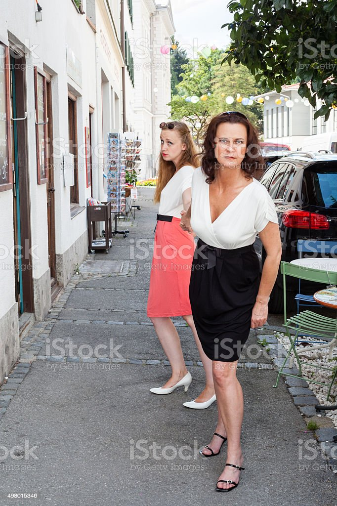 Determined Woman Tugging on Friends Hand stock photo