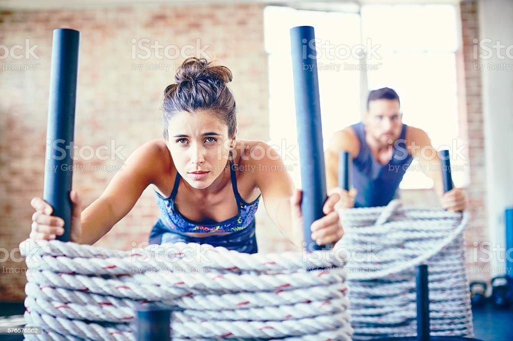 Determined woman with instructor working out on rope sled stock photo