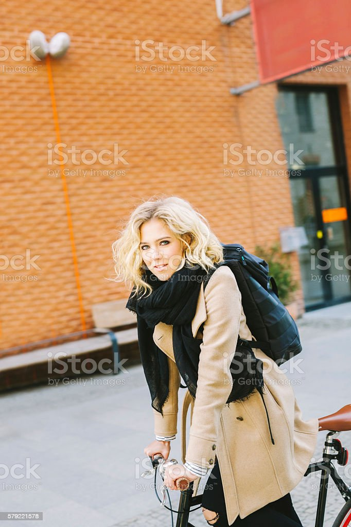 Determined Young Woman On A Bicycle In A Modern District stock photo