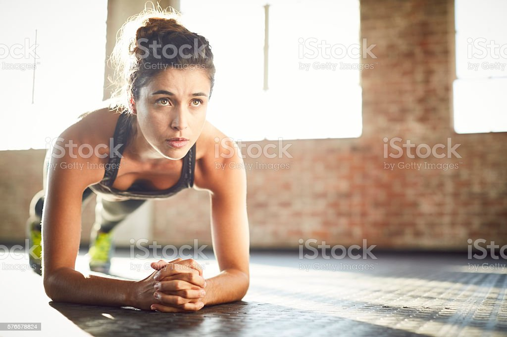Determined young woman performing plank position in gym stock photo