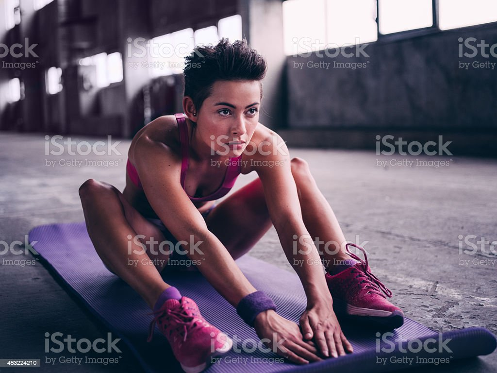 Determined young woman sitting on a colourful exercise mat stock photo
