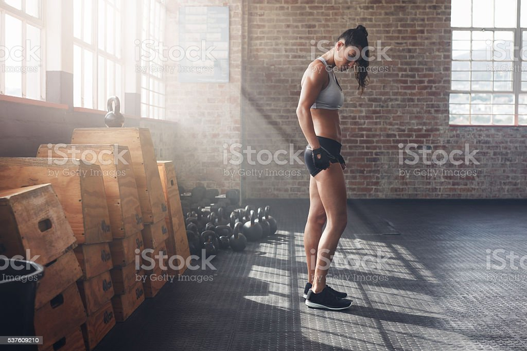 Determined young woman standing in gym stock photo