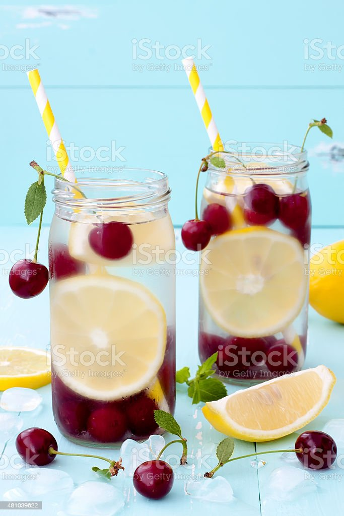 Detox fruit infused flavored water with cherry, lemon and mint stock photo