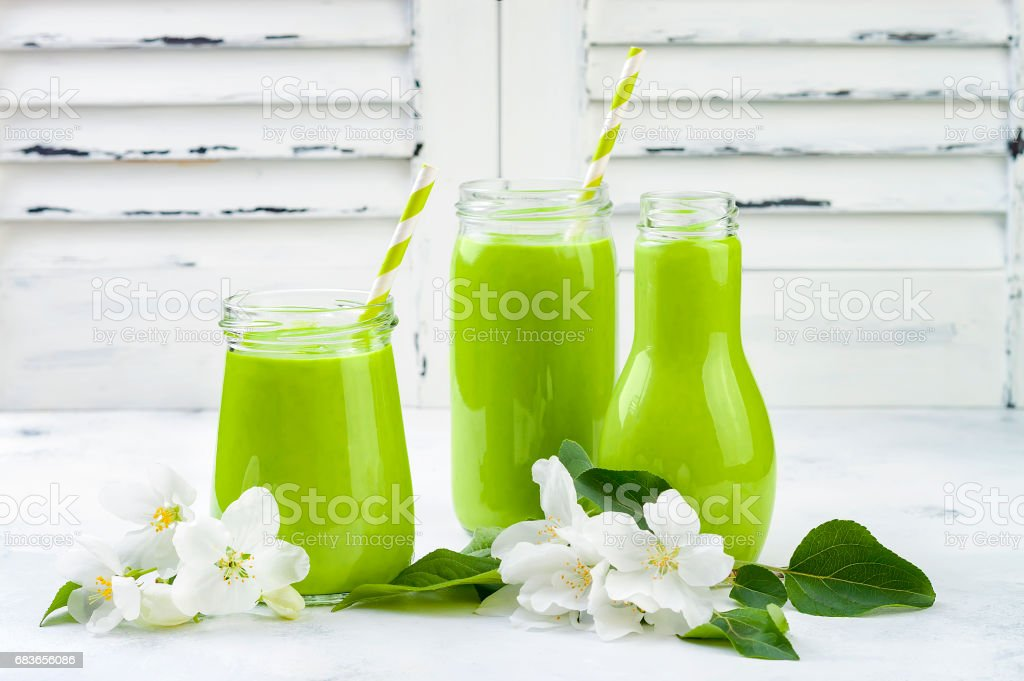 Detox, healthy green smoothie in jars and bottle. White wooden rustic background with apple blossom stock photo