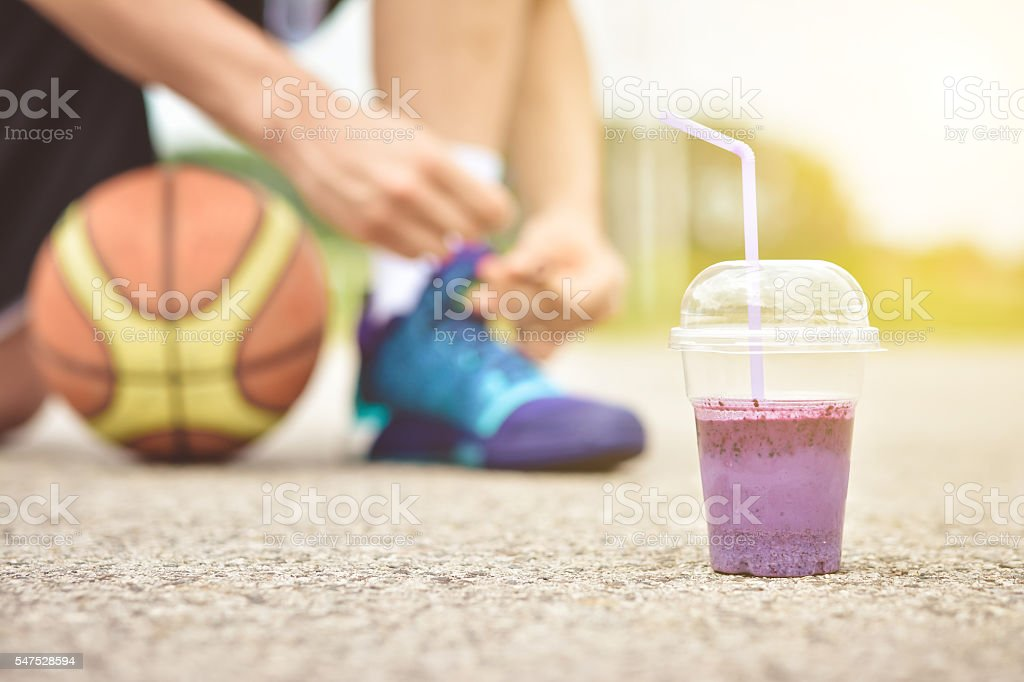 Detox smoothie drink and running footwear close up. stock photo