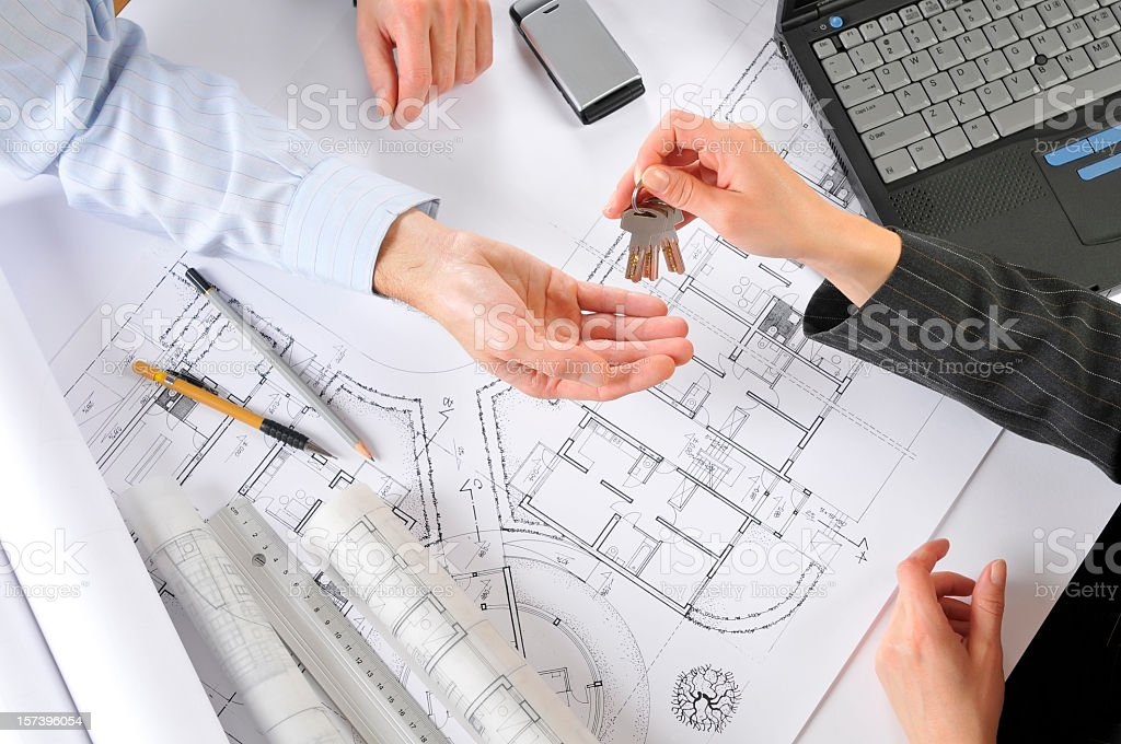 Developer giving new house keys to the client, building plans royalty-free stock photo
