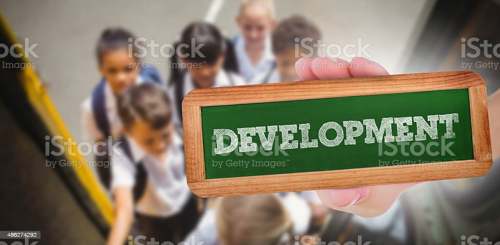 Development against cute schoolchildren getting on school bus stock photo