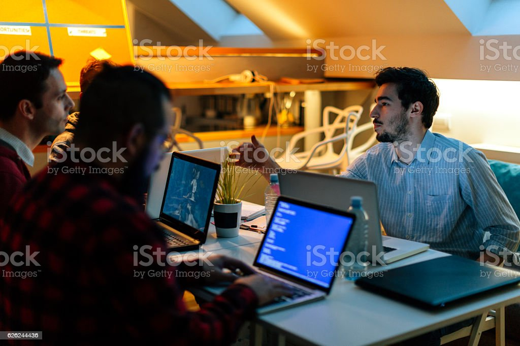 Development Team Working Late In Their Office. stock photo