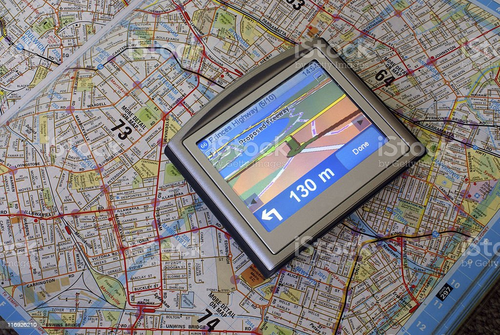 A GPS device showing directions on a paper map stock photo