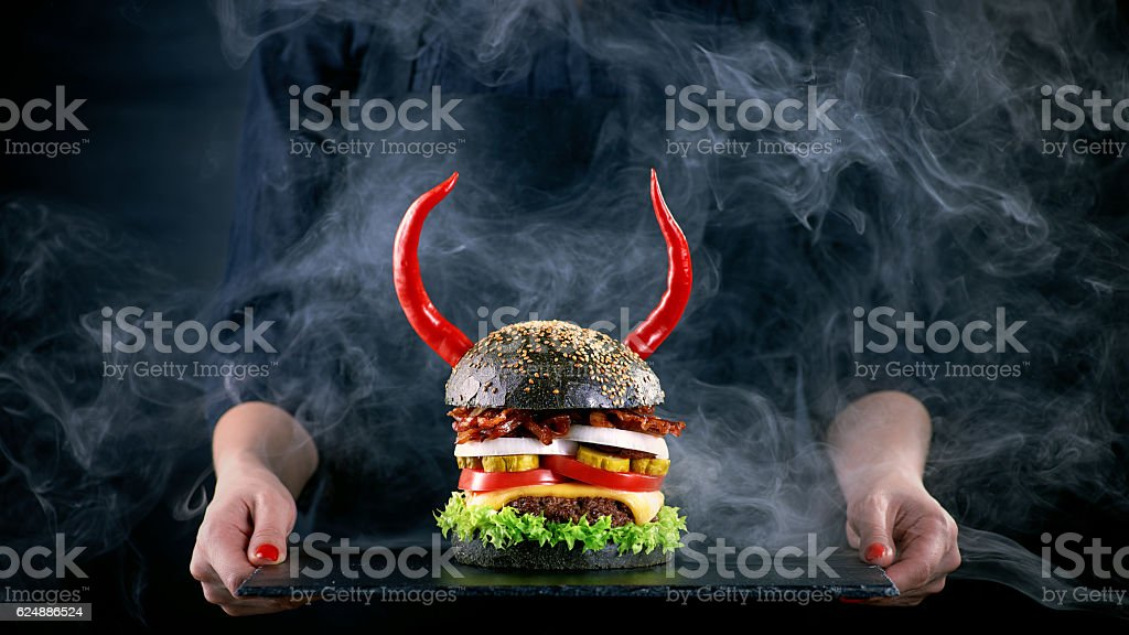 Devil burger with bacon and vegetables on black slat plate stock photo