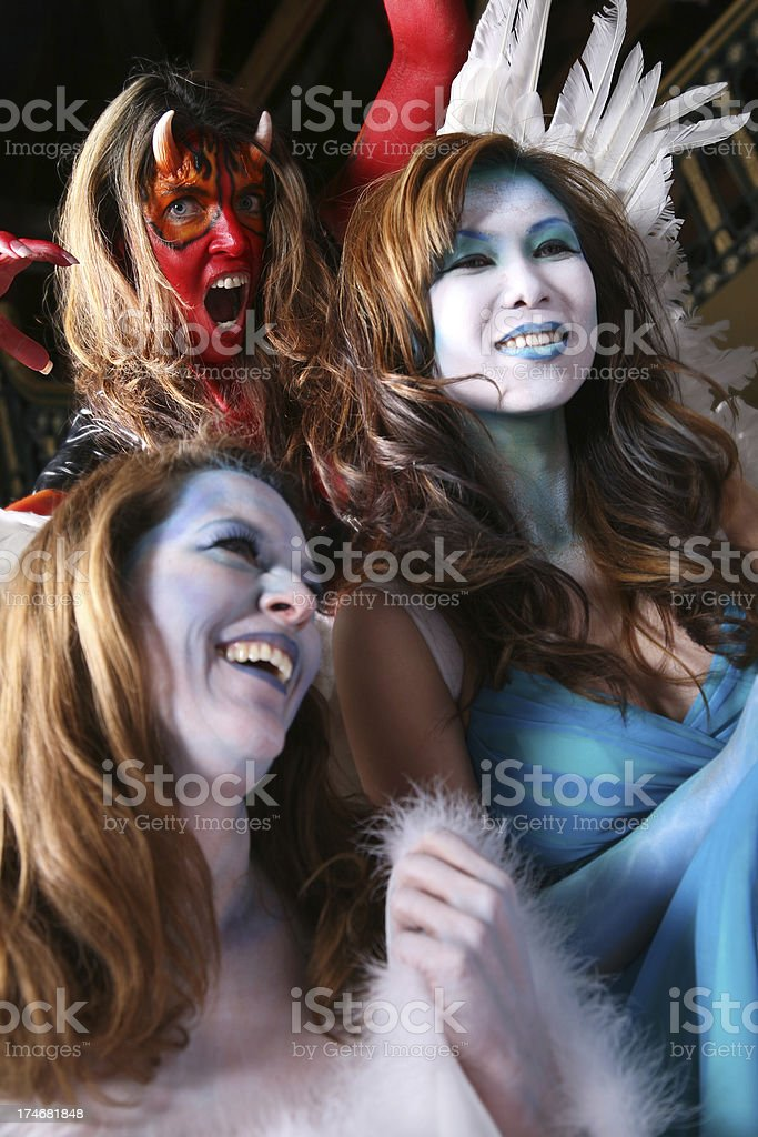 Devil Sneaking Up on Happy Angles stock photo