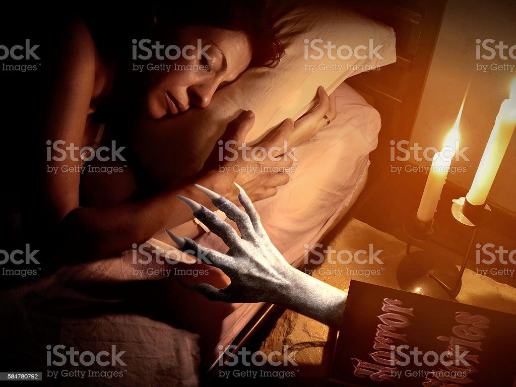 devil vampire hand grabbing sleeping woman stock photo