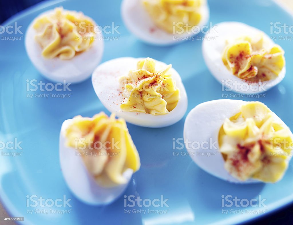 deviled eggs on colorful blue plate stock photo