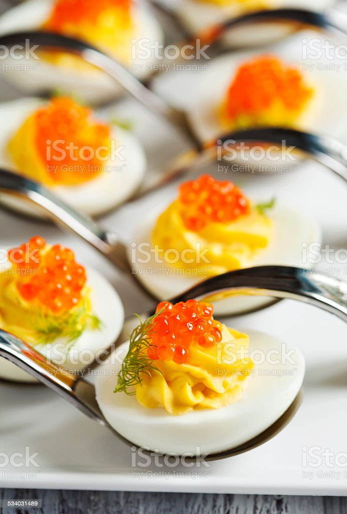 Deviled eggs with red caviar in a spoon stock photo