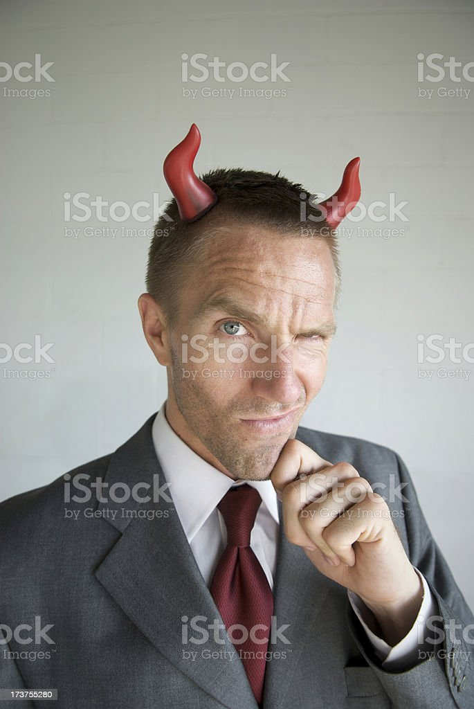 Devilish Businessman with Devil Horns Smirking stock photo