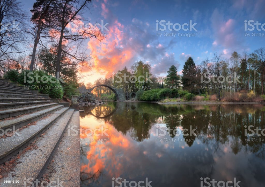 Devil's Bridge in Kromlau, Germany. Amazing landscape with Rakotz Bridge, stairs, lake, green trees, colorful blue sky with multicolored clouds reflected in water at sunset in spring. Rakotzbrucke stock photo