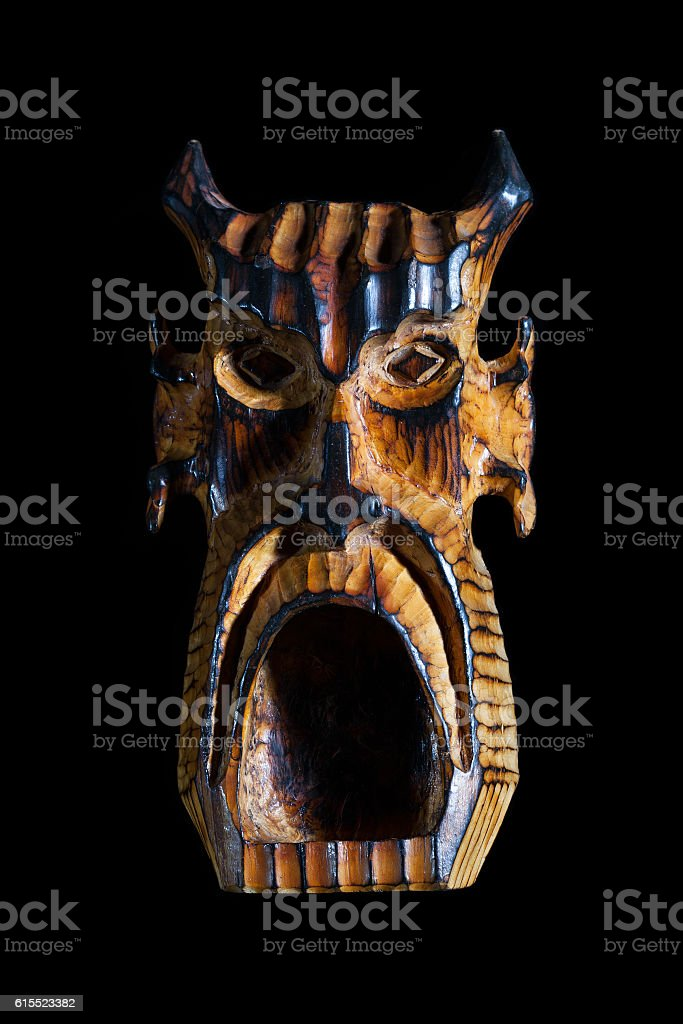devils mask with open mouth made of wood stock photo