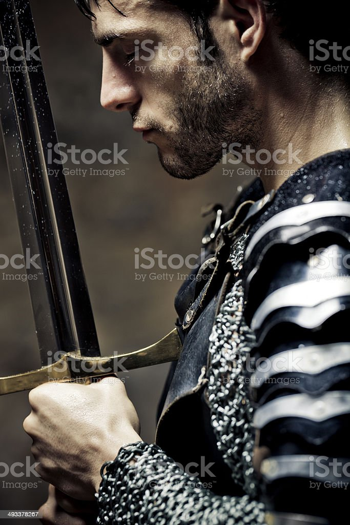 Devote medieval knight in the darkness stock photo