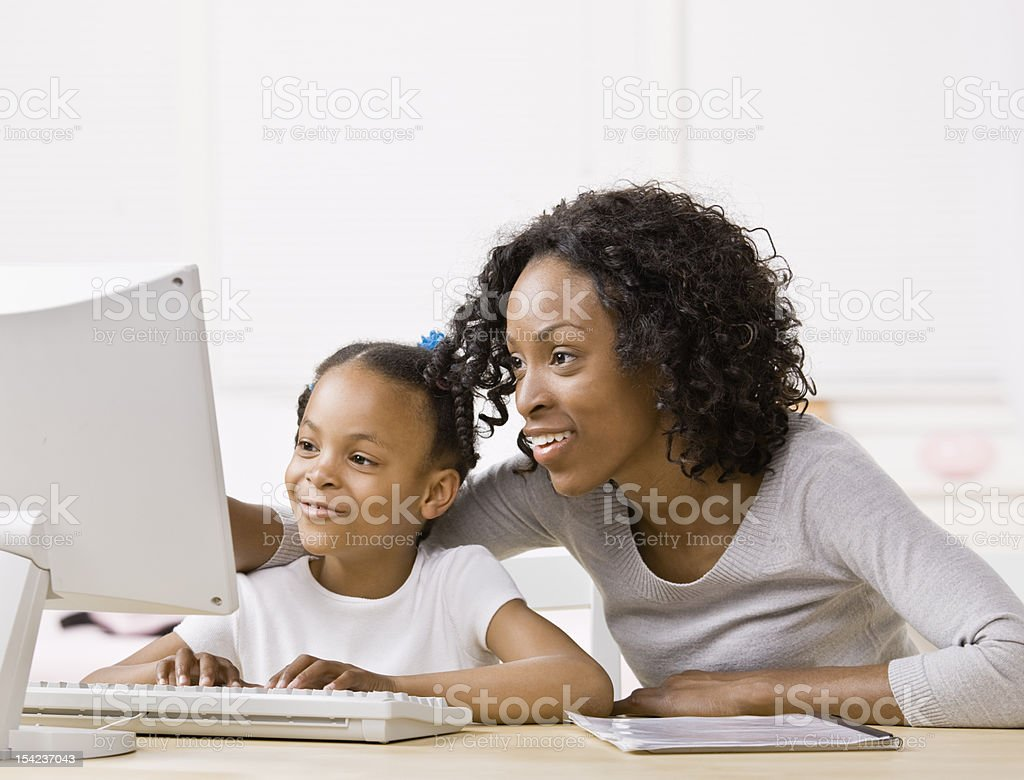 Devoted mother helping girl do homework on computer stock photo