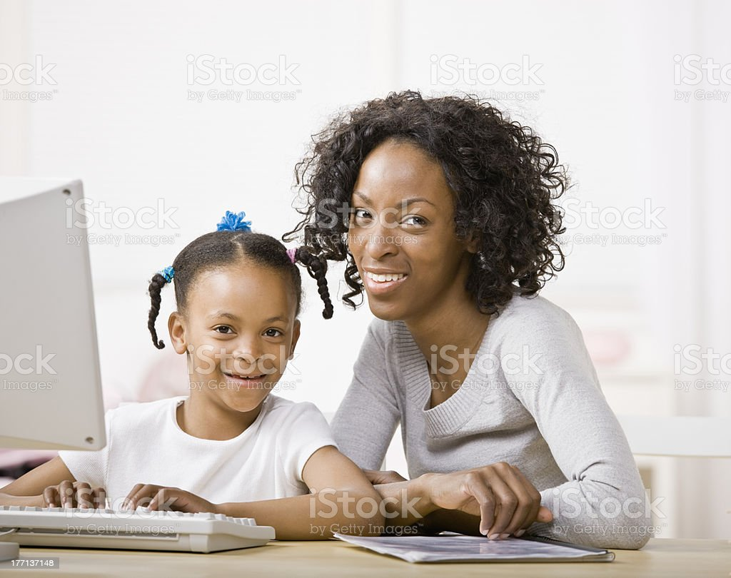 Devoted mother helping girl do homework on computer royalty-free stock photo
