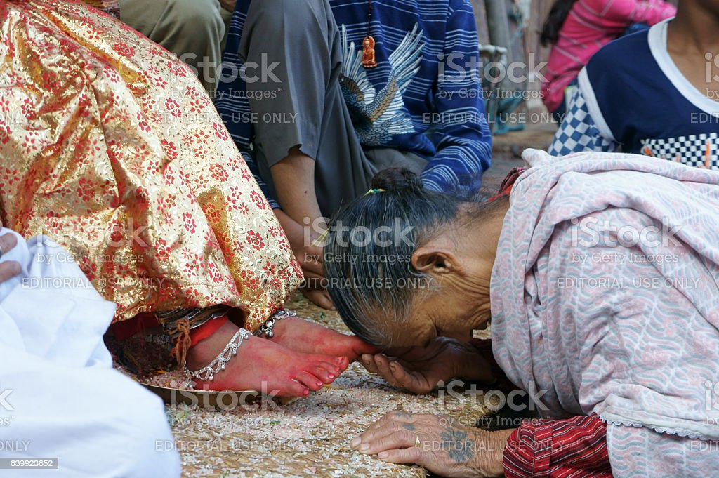 devotee touching feet of Kumari stock photo