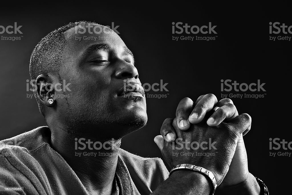 Devout African-American man praying fervently in black-and-white portrait stock photo