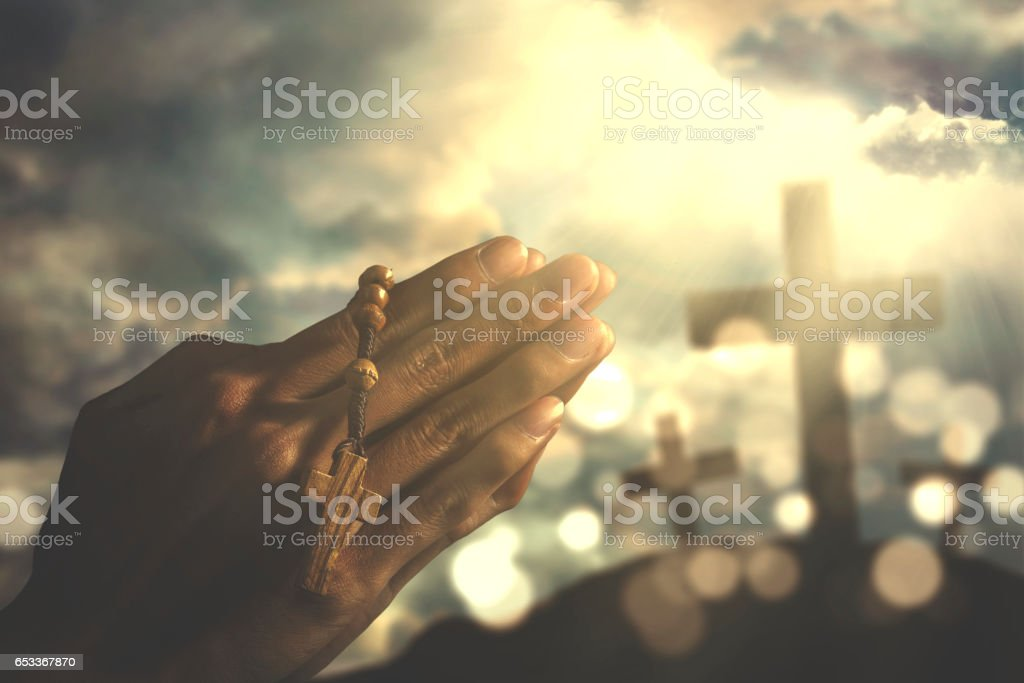 Devout person praying with rosary stock photo