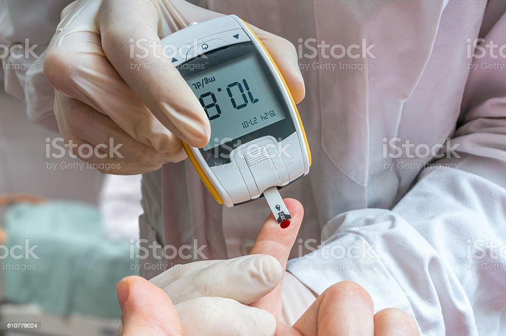 Diabetes concept. Doctor is monitoring blood glucose level of patient. stock photo