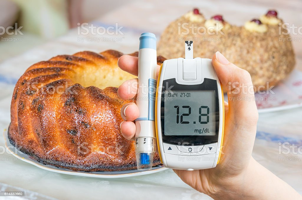 Diabetes, diet and unhealthy eating concept. Hand holds glucometer. stock photo