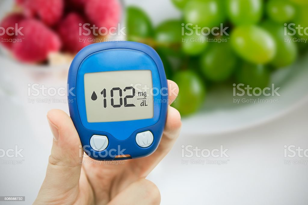 Diabetes doing glucose level test. Fruits in background stock photo