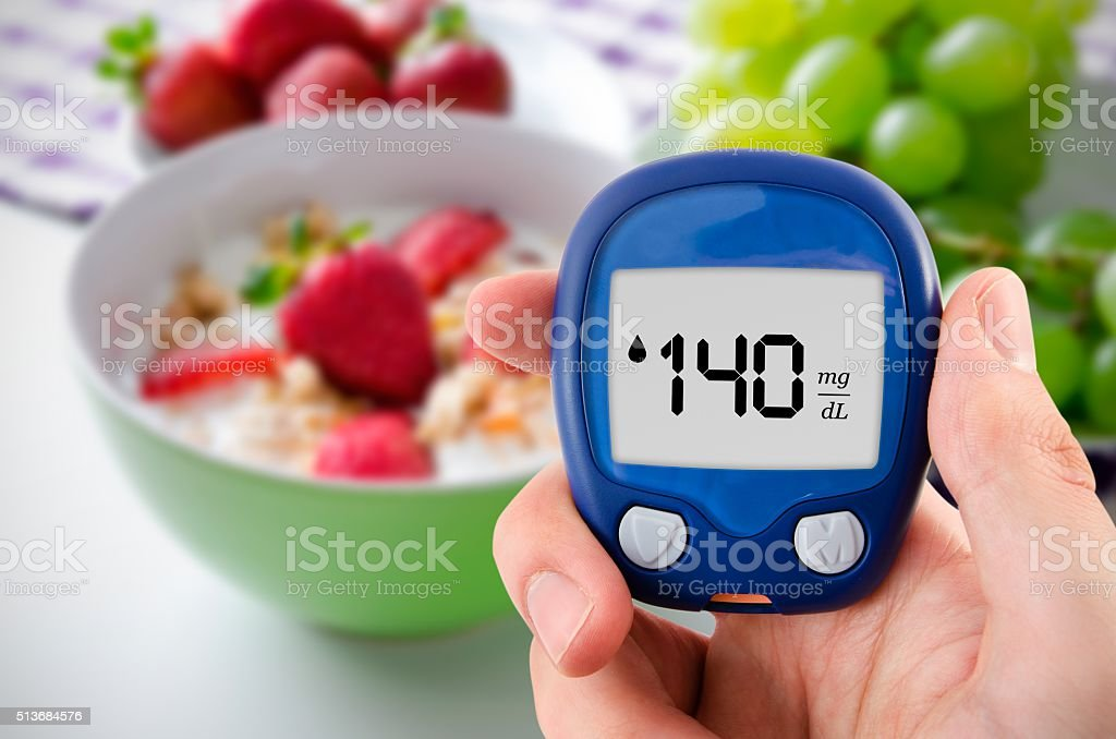 Diabetes doing glucose level test. Fruits in background stock photo