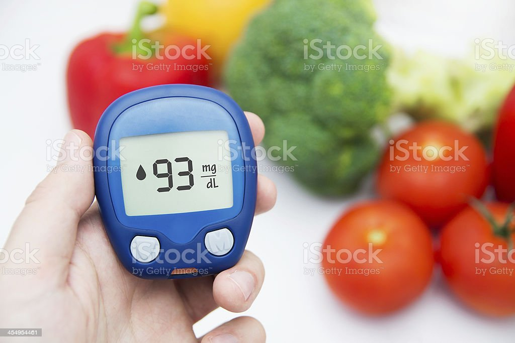Diabetes doing glucose level test. Vegetables in background stock photo